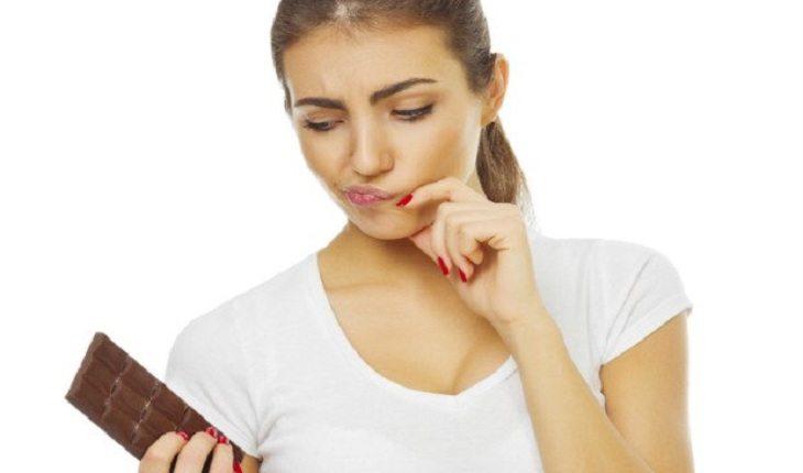 mulher olhando com rosto de insatisfação para uma barra de chocolate vida saudável