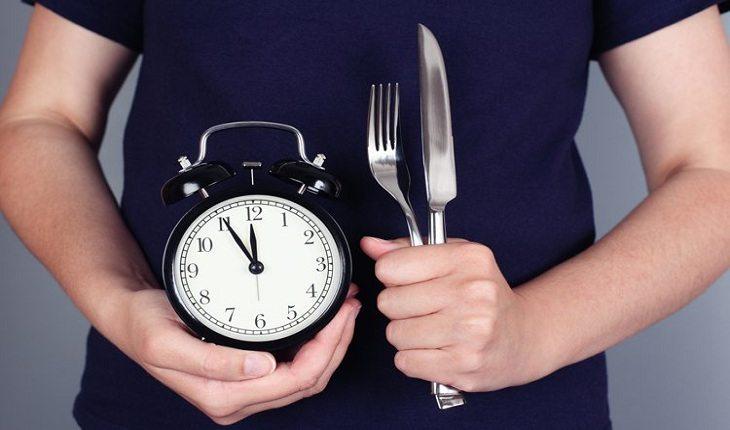 pessoa segurando um relógio e um garfo e faca vida saudável