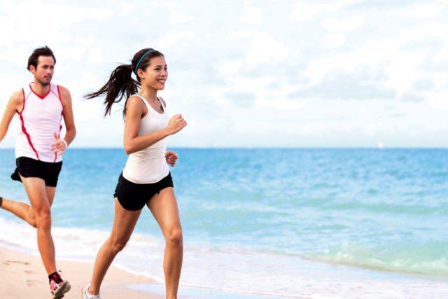 homem e mulher em corrida na praia