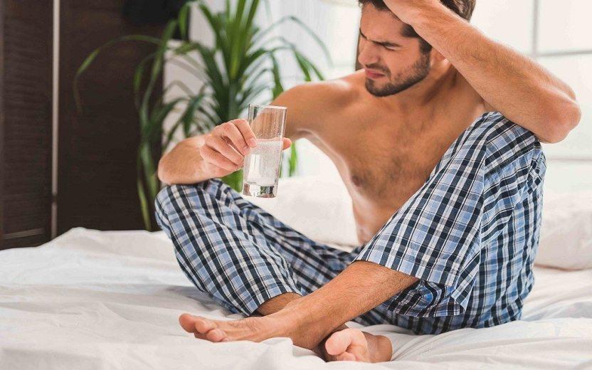 Homem sentado em cama sofrendo de ressaca