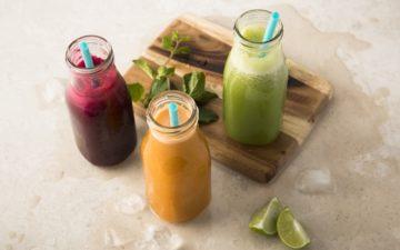 Sucos funcionais: três receitas. Na foto, três garrafas de suco, um verde, um laranja e um roxo.