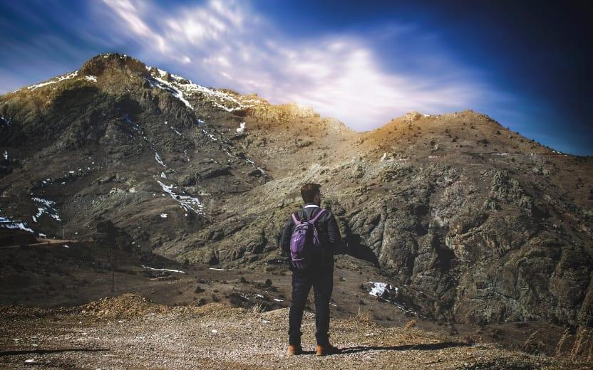 Homem parado em montanha após ter praticado seu trail running
