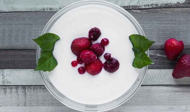 Ingestão de proteínas: na foto, uma foto de um copo de iogurte com frutas vermelhas visto de cima.
