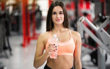 Ingestão de proteínas. Mulher na academia segurando uma garrafa de água