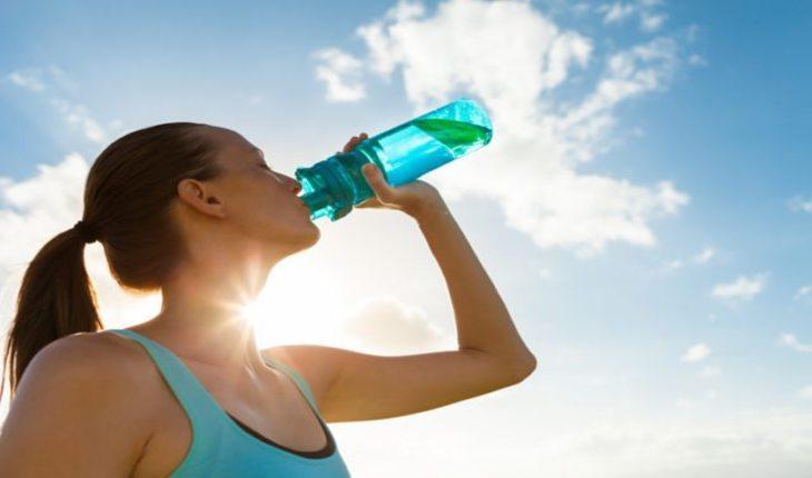 mulher bebendo água pre-treino