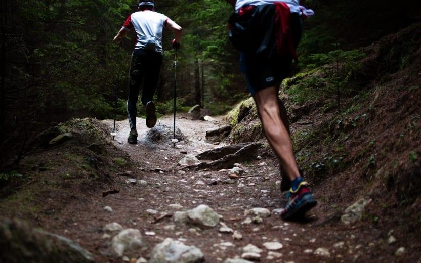 Homens correndo um trail running pesado em floresta fechada