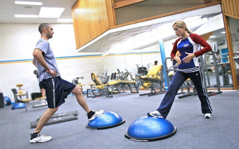 Imagem de duas pessoas em uma academia, um homem e uma mulher, realizando exercícios com um Bosu no chão. BosuBosu