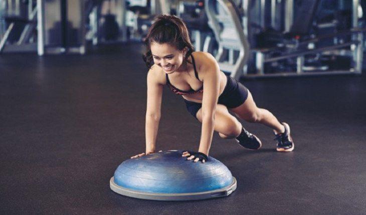 Imagem de uma mulher em uma academia realizando um abdominal escalador com um bosu. Bosu