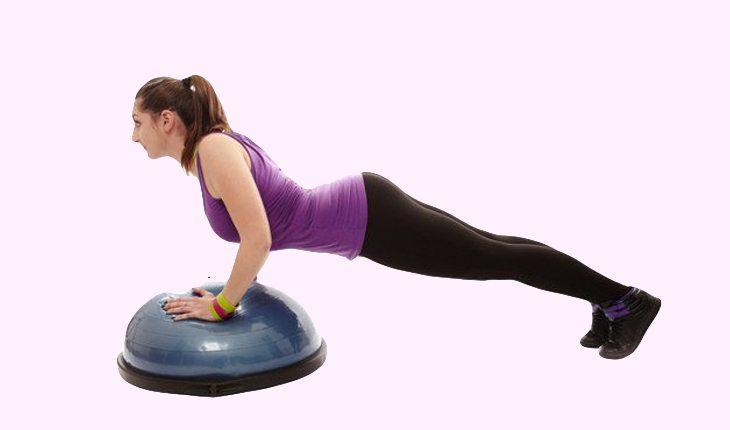 Imagem de uma mulher em uma academia realizando uma flexão com os braços fechados com um bosu. Bosu