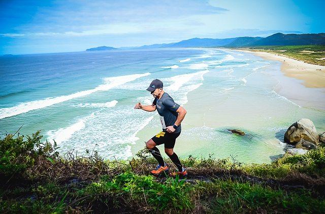 Atleta durante a participação na prova, percorrendo uma trilha em uma montanha da praia do Santinho