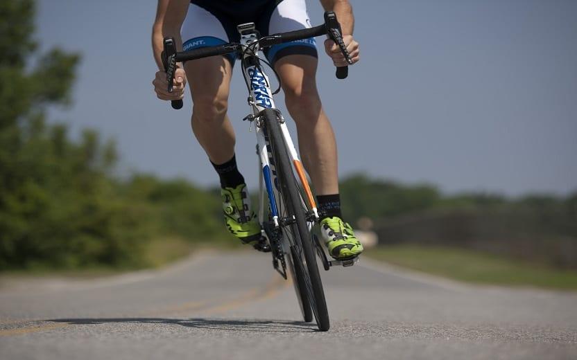 Pessoa pedalando de bike na estrada. Pedalar ajuda a correr mais rápido