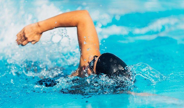 homem nadando ao estilo crawl com a cabeça virada para respirar