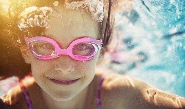 a foto mostra uma menina sorrindo ambaixo da água com um óculos de natação rosa