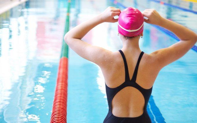 mulher com maiô e uma touca rosa à beira da piscina arrumando seus óculos, ilustrando alguém que busca os benefícios da natação