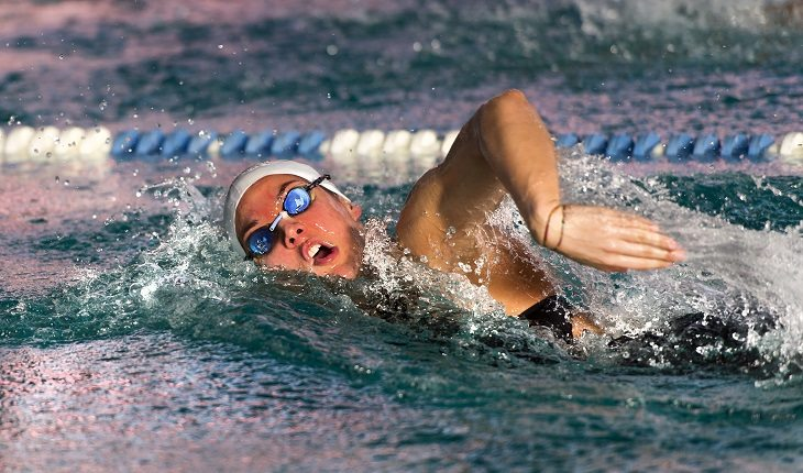 Equipamentos de natação: mulher nadando com touca e óculos