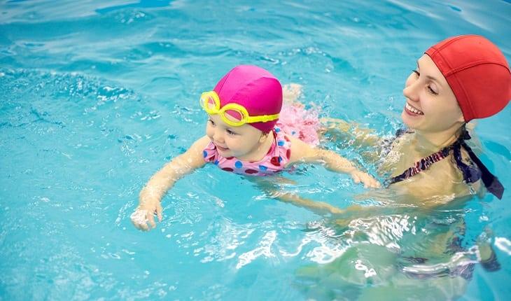 mulher segurando bebê nadando