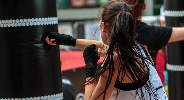 Para combater o estresse, é muito importante fazer exercícios físicos. Na foto, uma mulher está em uma academia, com o cabelo preso e suado, usando roupas de ginástica, dando socos em um saco de pancadas