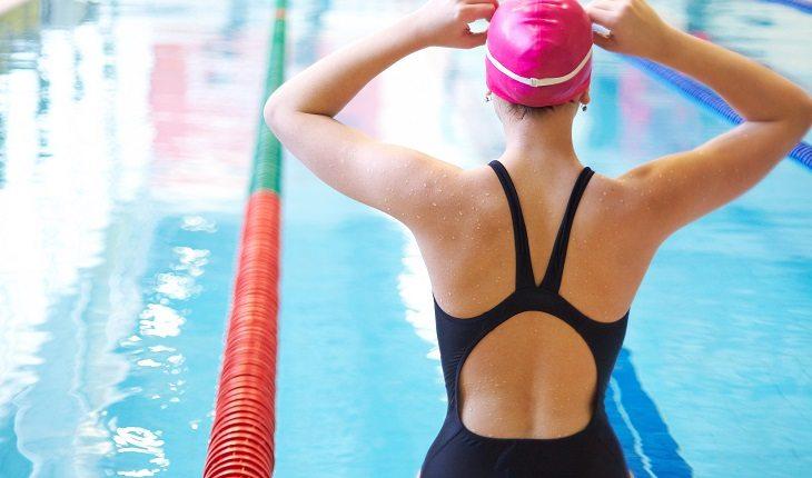 Equipamentos de natação: mulher com touca, óculos e maiô