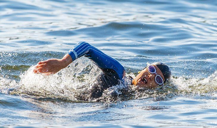 a foto mostra um homem nadando no mar