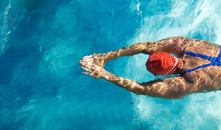 pessoa nadando com os braços esticados e uma touca vermelha