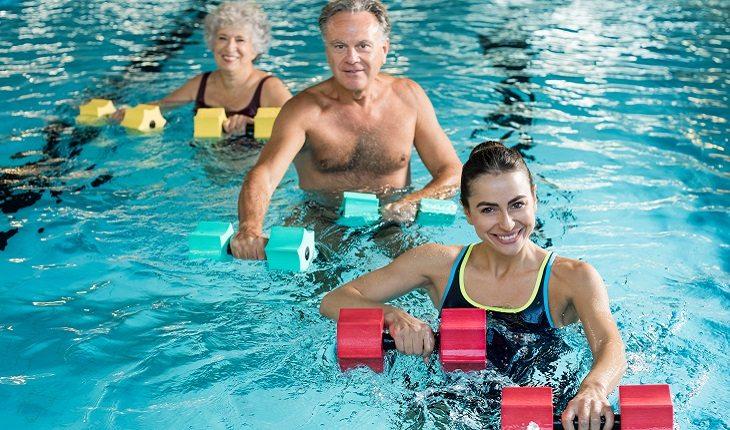 a foto mostra uma pessoa guiando a hidroginástica para duas pessoas idosas