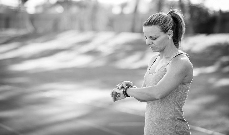 Corredora olha para o seu relógio durante o projeto de correr cinco quilômetros