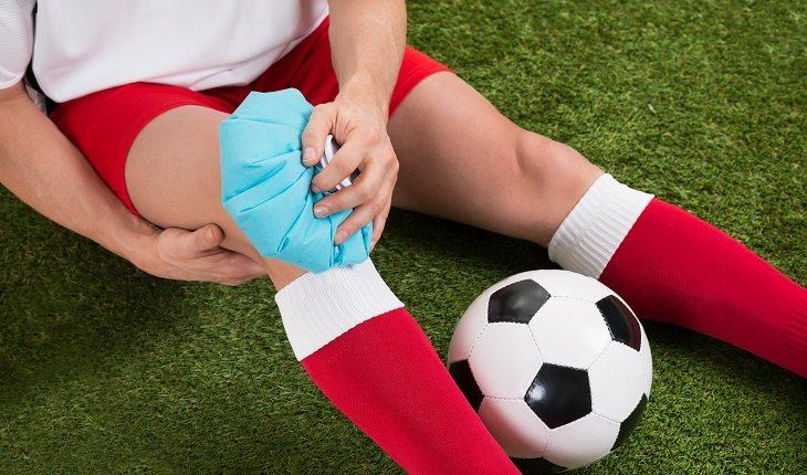 gelo ou compressa quente? Na foto, gelo sendo colocado no joelho de uma pessoa que estava jogando futebol