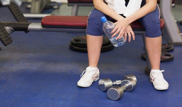 foto de uma pessoa sentada na academia, tomando água, descansando entre os exercícios