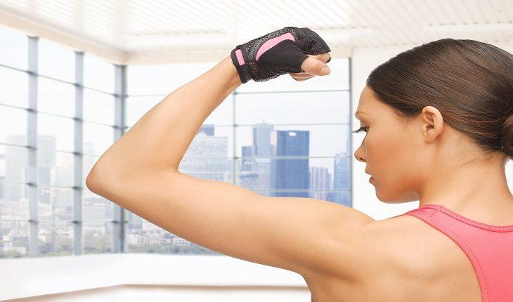 foto de uma mulher de costas, mostrando seu bíceps contraído