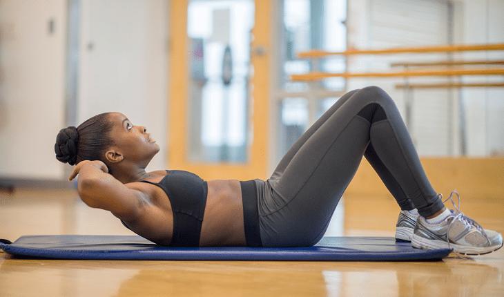 Treino de abdominal: mulher fazendo o exercício tradicional