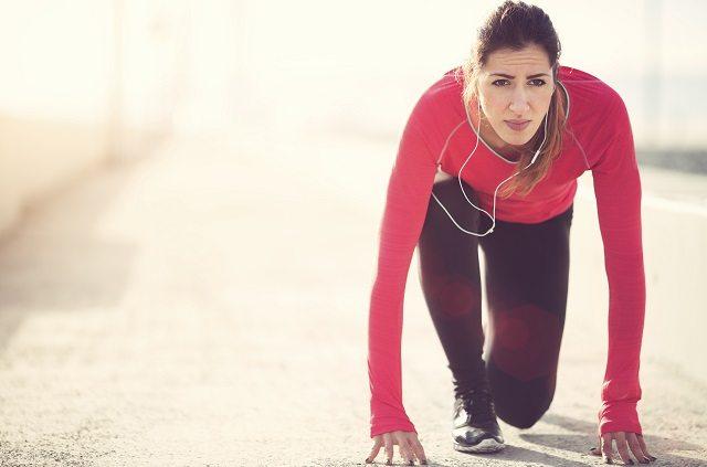 Na foto, uma mulher está em posição inicial para corrida. Para treinar no inverno, está com roupas de frio