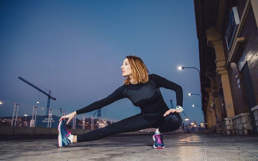 Treino de pernas completo. Na foto, uma mulher, na rua, aquecendo e alongando a perna