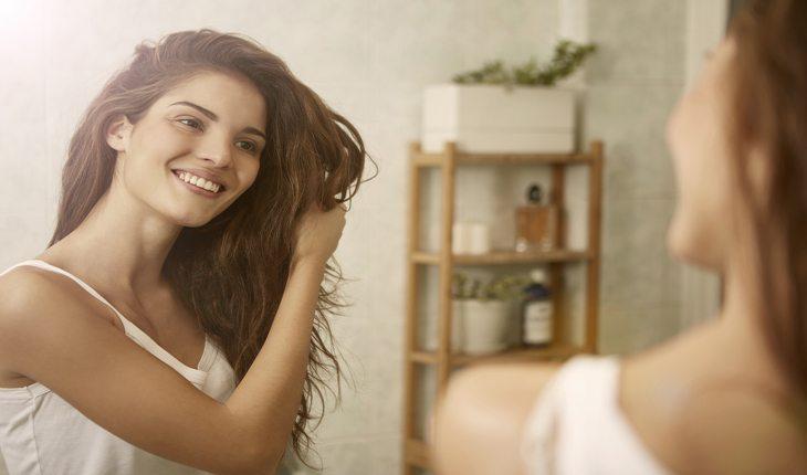 imagem de uma mulher segurando seus cabelos damasco