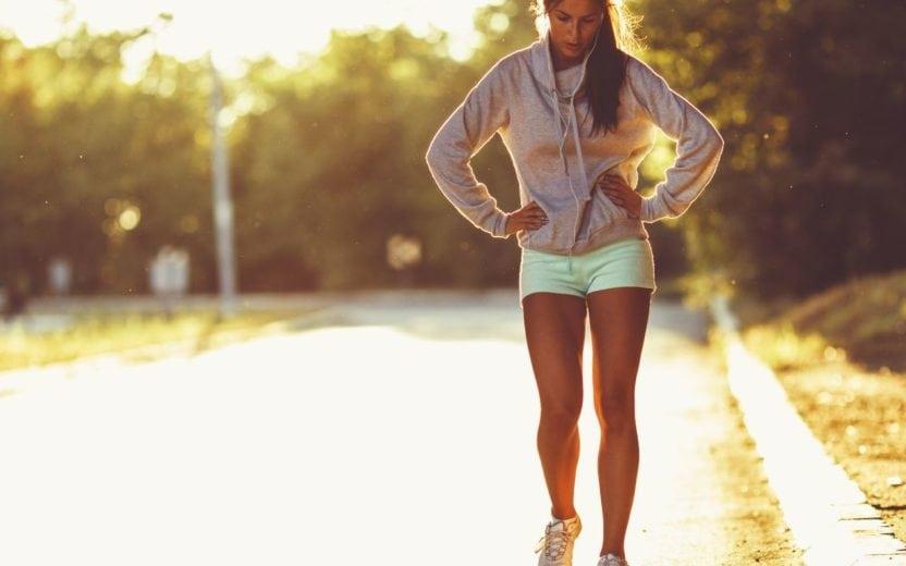 mulher cansada após uma corrida com as mãos em sua cintura dicas para longão