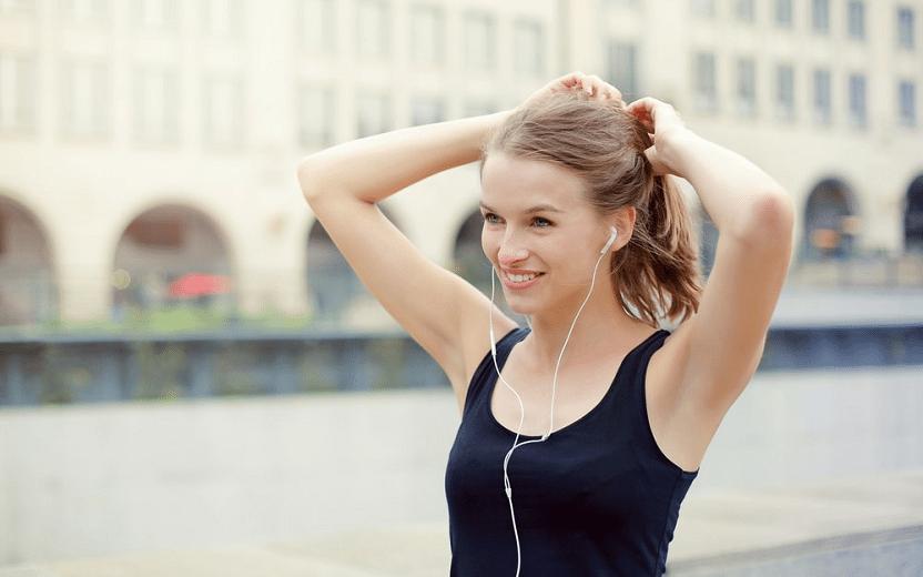 Alimentos que previnem queda de cabelo. Na foto, uma mulher que está se exercitando arruma o rabo de cavalo