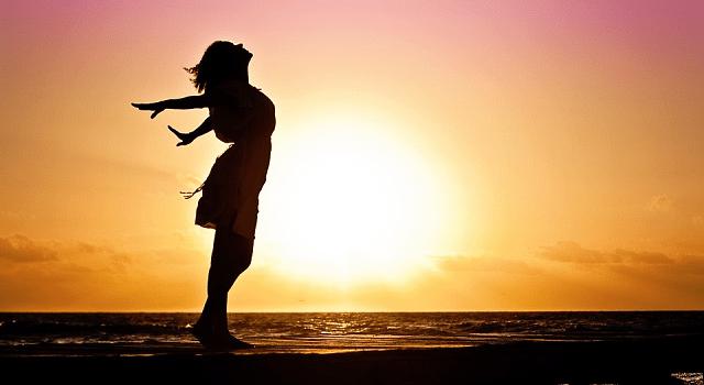 Aplicativo para fortalecer a autoestima. Na foto, uma mulher de vestido está feliz, com os braços abertos, com o pôr do sol ao fundo
