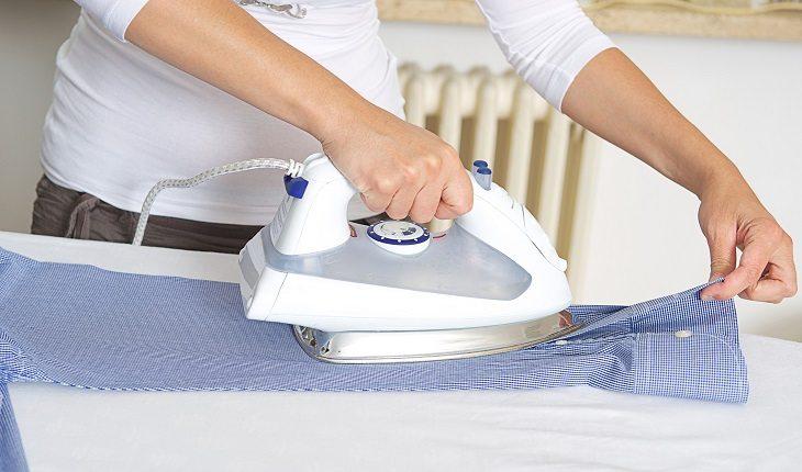 Na foto, uma mulher está passando roupa. Essa é uma das atividades domésticas que exige atenção quando o assunto é saúde da coluna