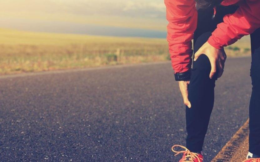 pessoa curvada com as mãos em sua perna direita dicas para longão