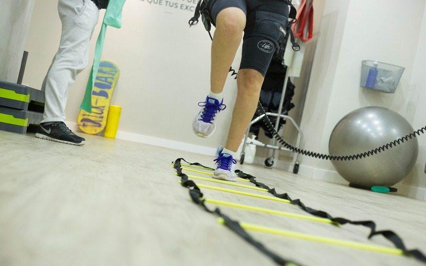 Imagem das pernas de uma pessoa em uma sessão de fisioterapia realizando exercícios. Atividades Físicas
