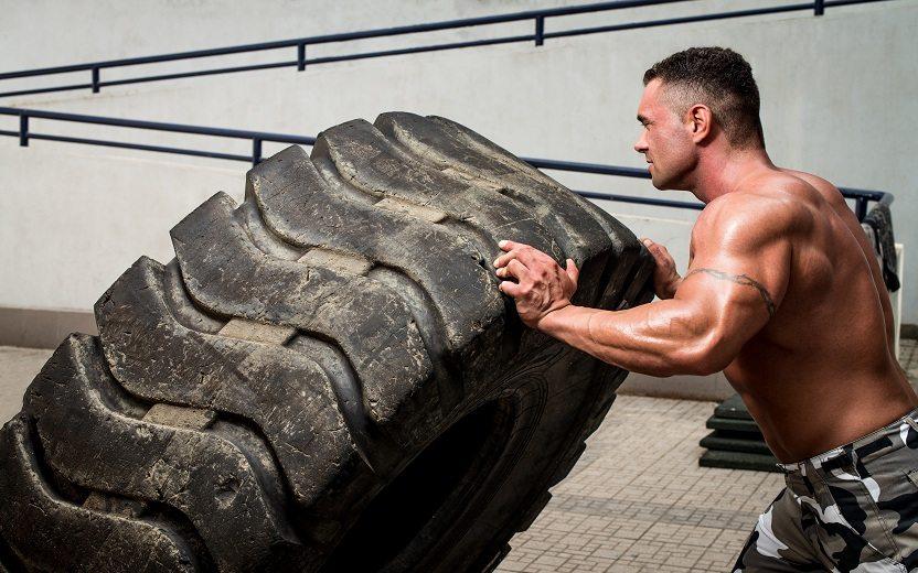 Homem sem camisa praticando um dos exercícios do CrossFit
