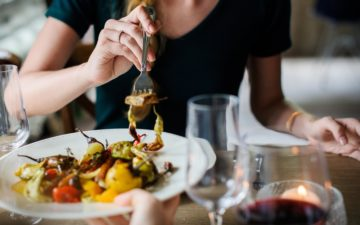 Imagem de uma mulher sentada em uma mesa jantando. Emagrecimento