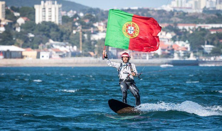 Português Francisco Lufinha com a bandeira de seu país, praticando kitesurf