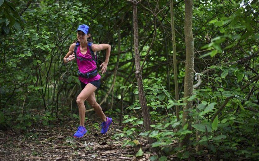 mulher correndo em meio a floresta ultramaratona