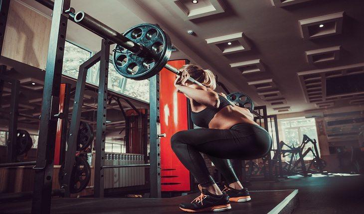 mulher fazendo agachamento com barra em uma academia