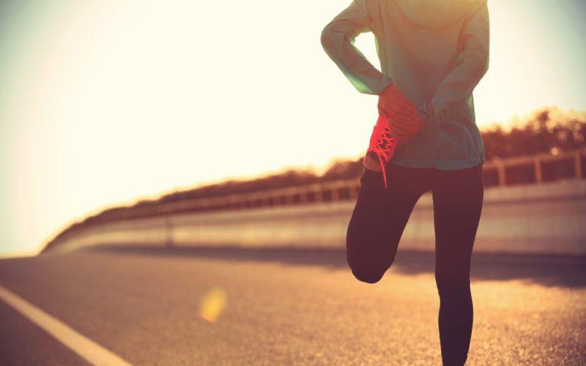 mulher se alongando em uma pista de corrida alongamento
