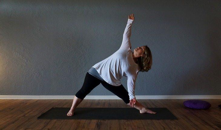 Imagem de uma mulher alongando em cima de uma esteira. Atividades físicas