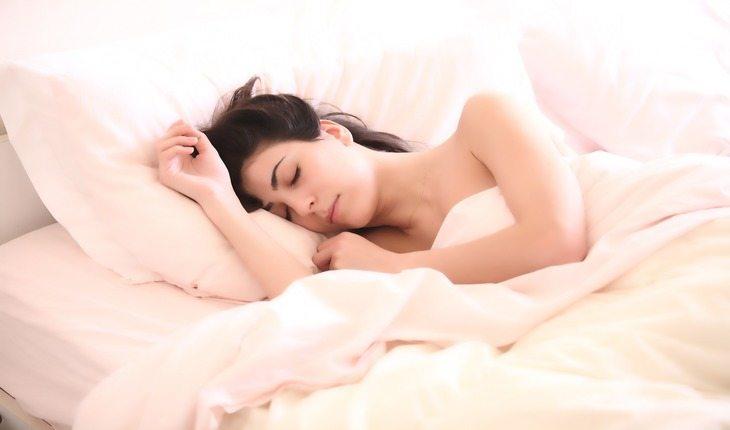 Imagem de uma mulher deitada em uma cama dormindo. Atividades físicas