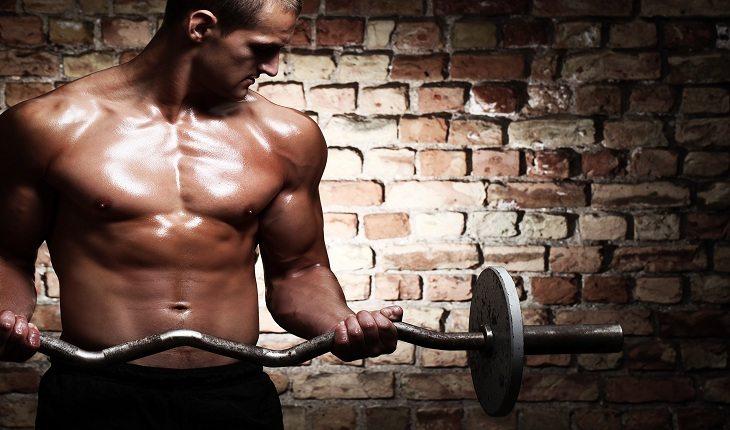 homem sem camisa executando exercício de bíceps com a barra