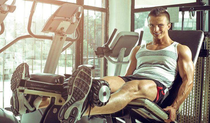 homem sentado em uma cadeira extensora treinando perna
