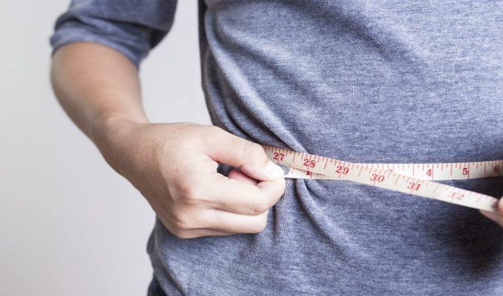 Imagem homem com fita métrica se medindo. Corrida
